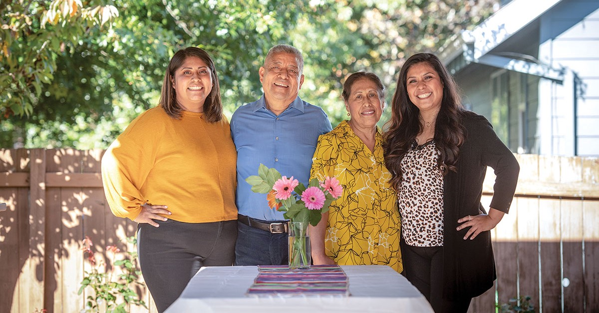 Three women and a man pose for a photo outside. A table with flowers is in front of them.