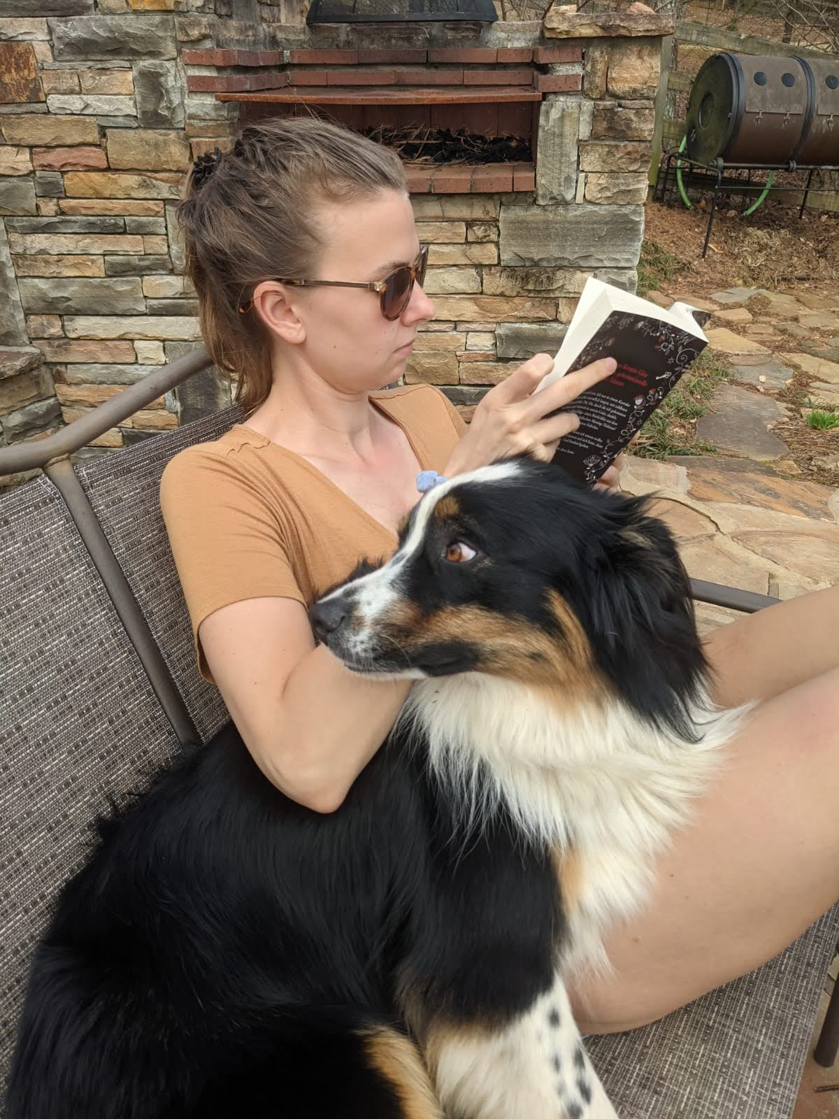 Image of author sitting outside on a bench reading with a dog at her side.