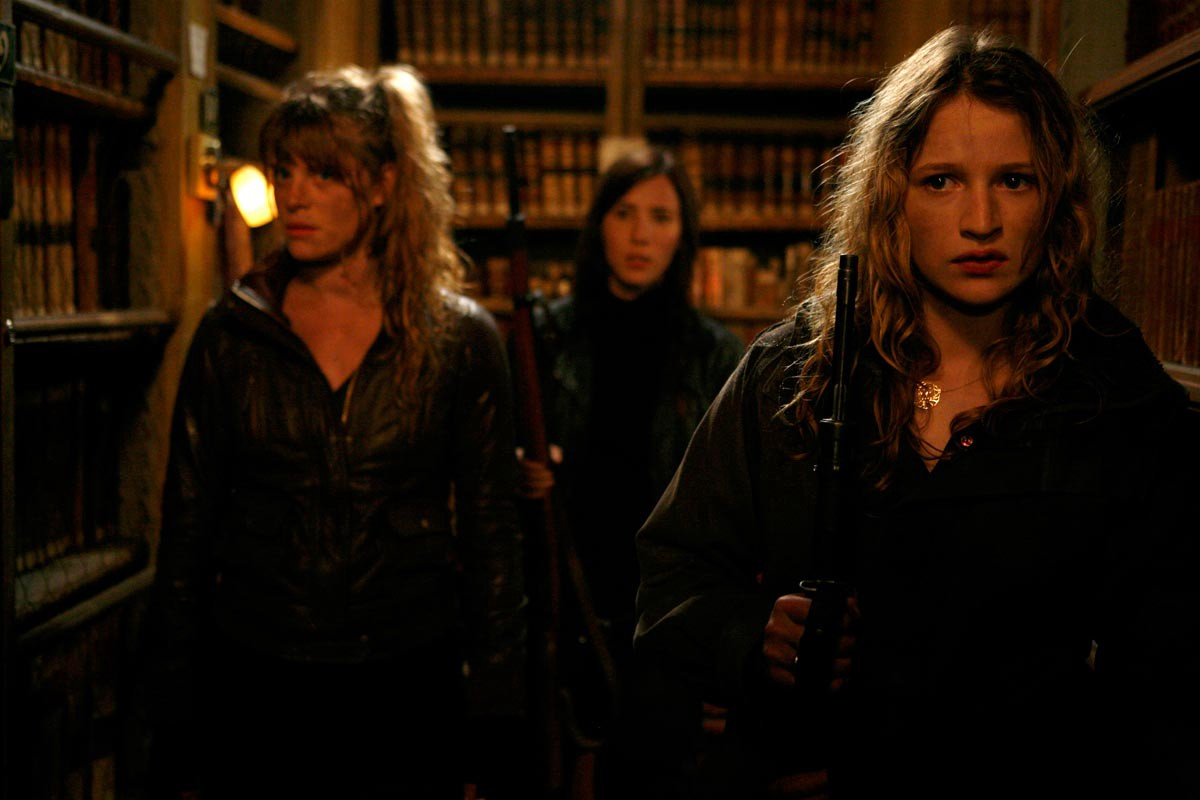 Three armed women are walking in a dimly lit library.
