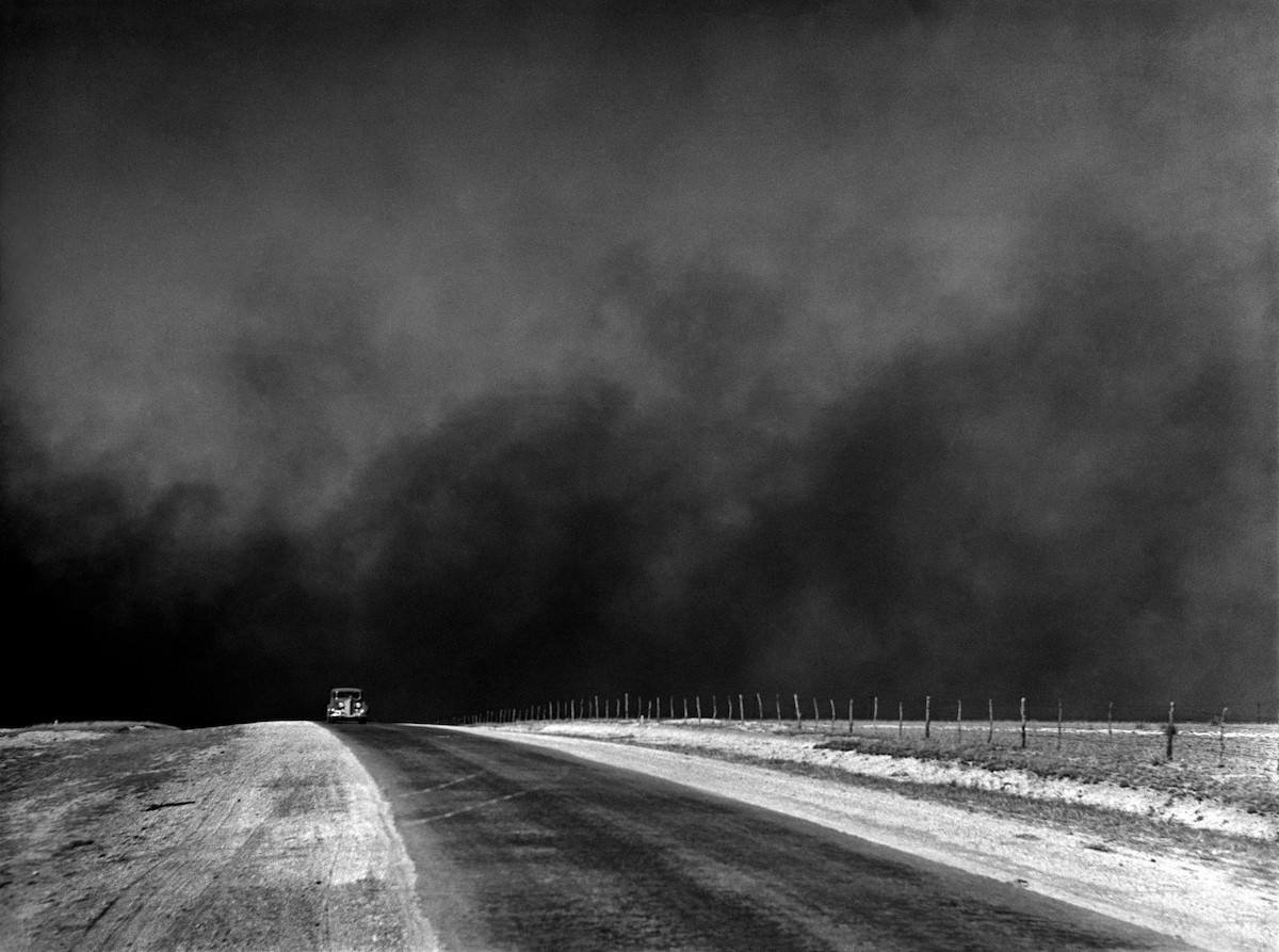"""A car drives ahead of a massive dust storm, known as a """"black blizzard,"""" in the Dust Bowl era."""
