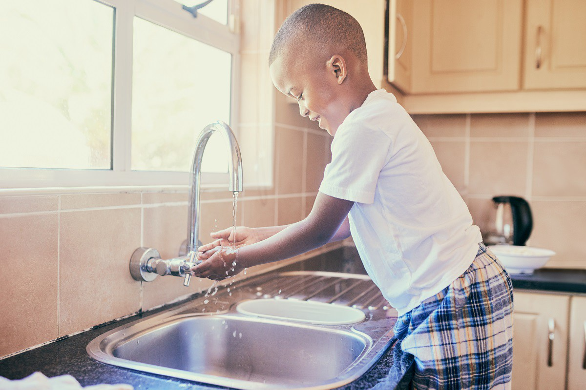 A young boy washes his hands.