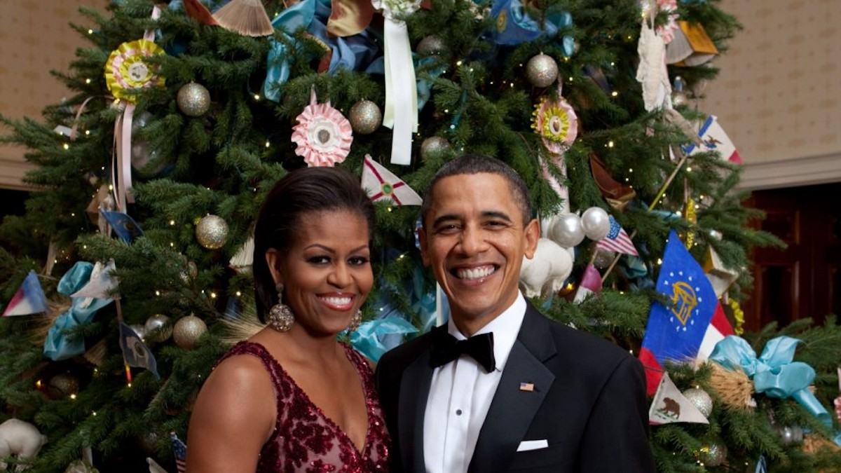 Michelle Obama, wearing a crimson evening gown, and Barack Obama, wearing a bow tie, pose in front of a large Christmas tree.