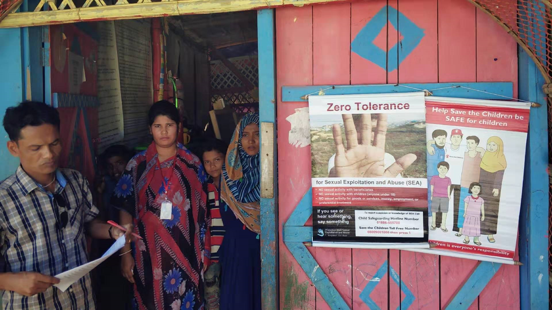 Workers and children stand outside of a learning center in Camp 14 of kutupalong rohingya refugee camp