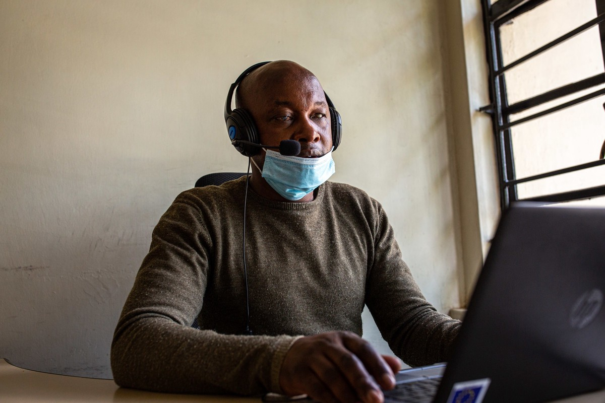 A man sits with head phones and a face mask on while working from a computer.