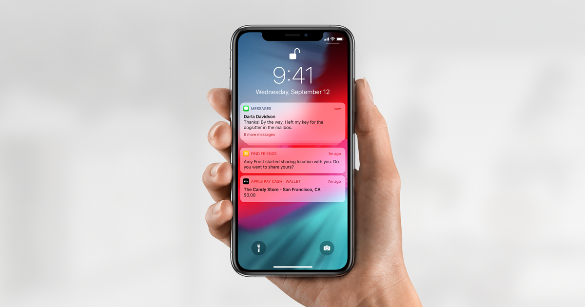 Person holding an unlocked iPhone with various notifications.