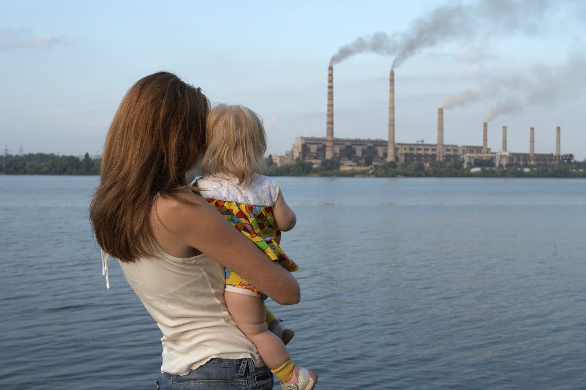 A mother and child look across the water at smokestacks.