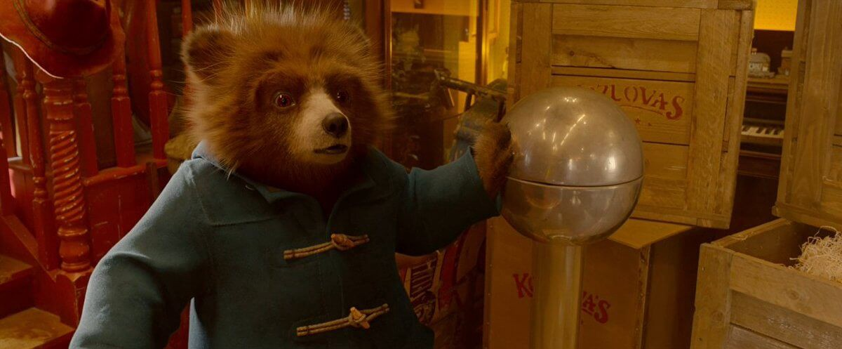 Paddington touching a device that makes his hair fuzz up.