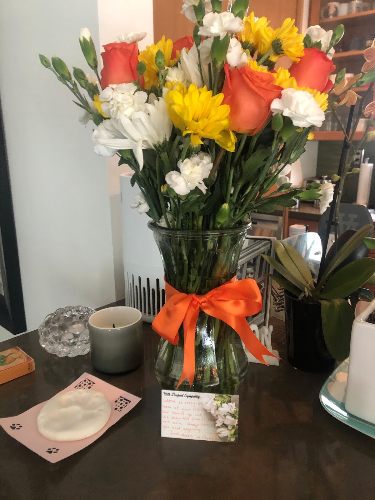 Picture of a bouquet of white, orange and yellow flowers on a dark brown wood dining room table.