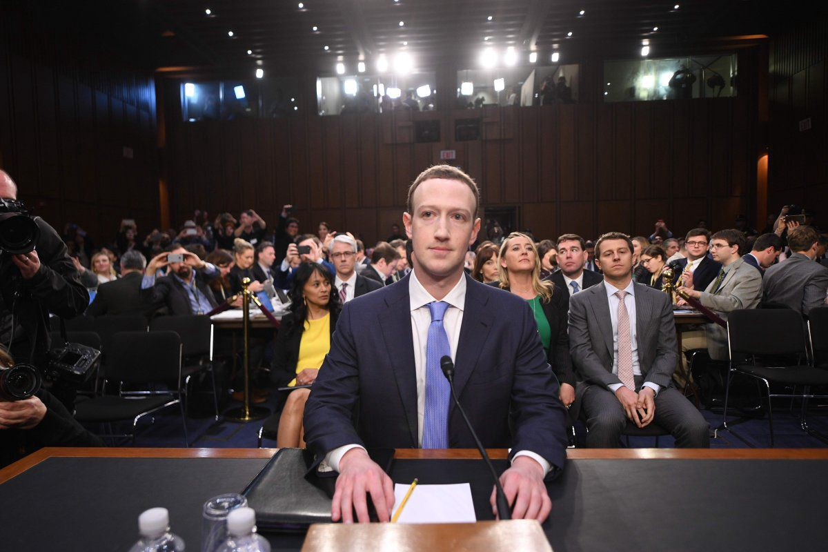 Facebook CEO Mark Zuckerberg sits at a desk with bright lights and people behind him