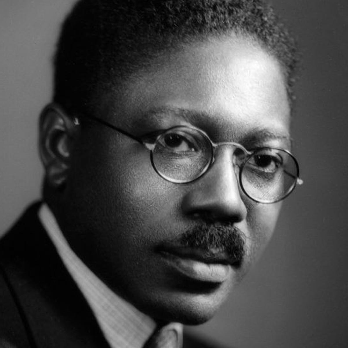 A black and white photograph of an African American Male—graphic designer Aaron Douglas. He is wearing round spectacles, he has a thick moustache and he wears a black and white suit, with a white dress shirt and black dress jacket.