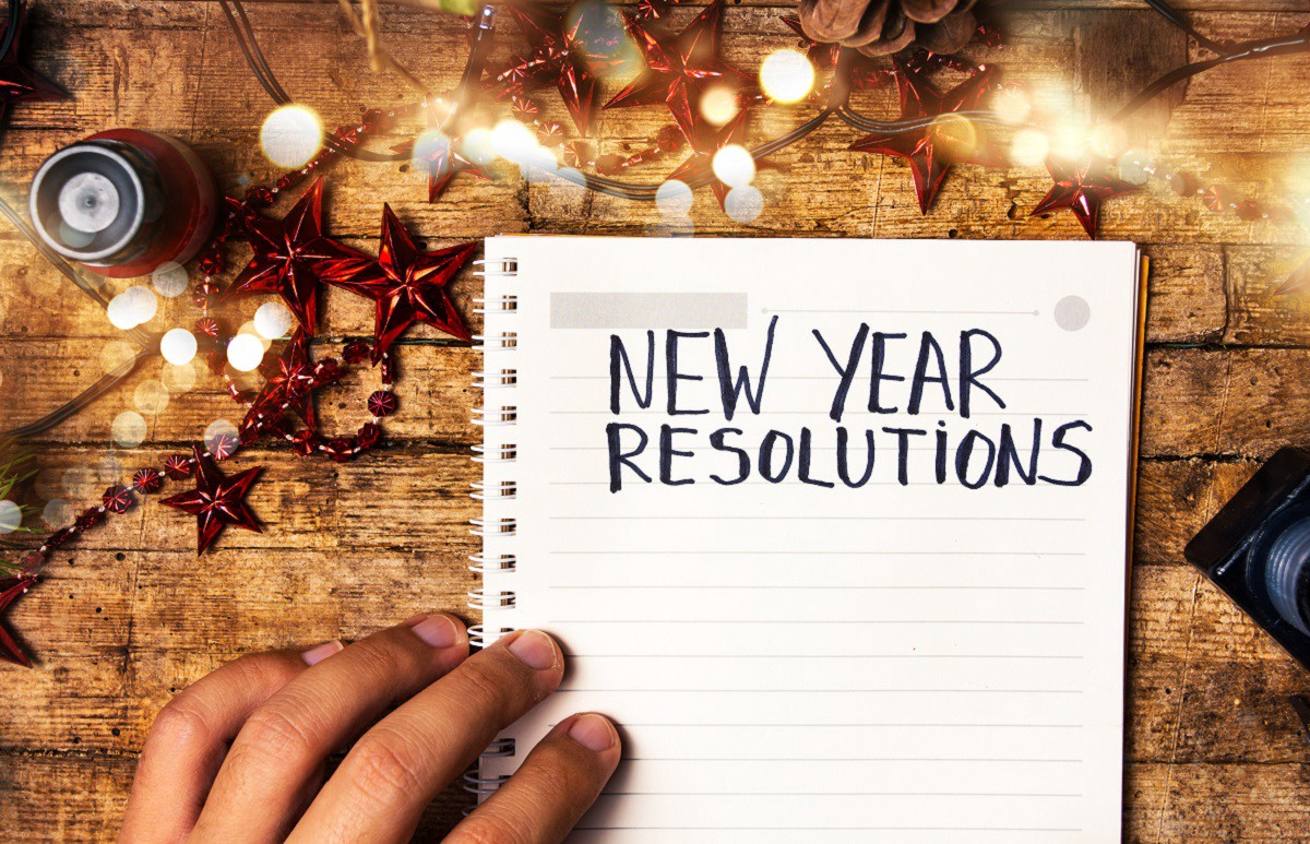"An notebook open to a mostly blank page. ""New Year Resolutions"" is written on top."