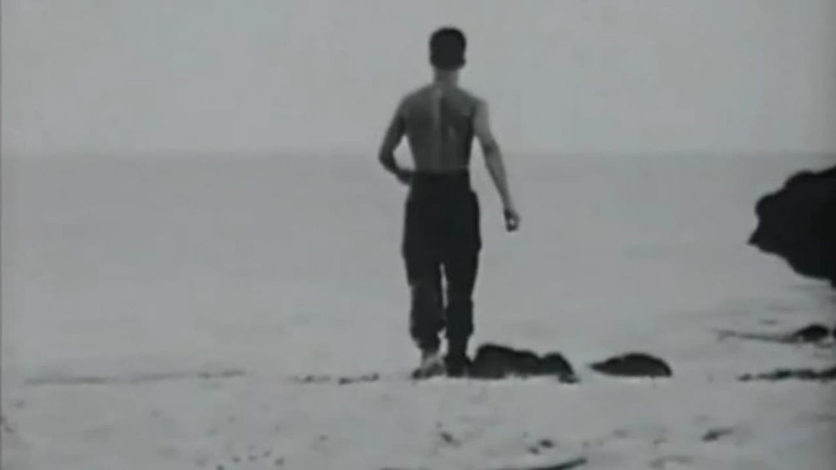 A man is seen turning is back to the camera, wlaking towards the sea. Black and white.