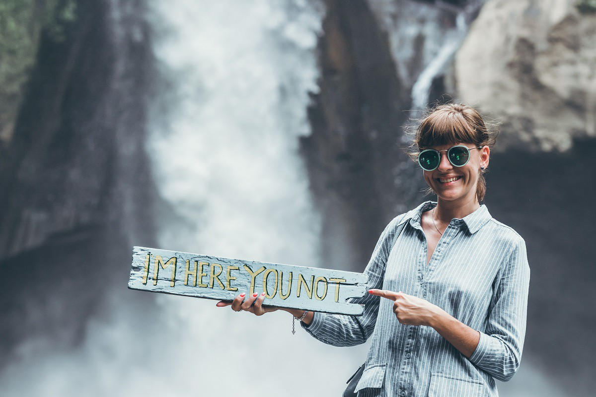 """Woman standing in front of a beautiful waterfall with a sign that reads, """"I'm Here You Not."""""""