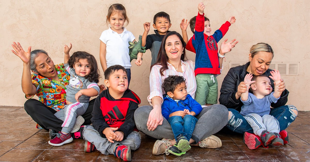 Child care provider Miren Algorri surrounded by children and her co-workers.