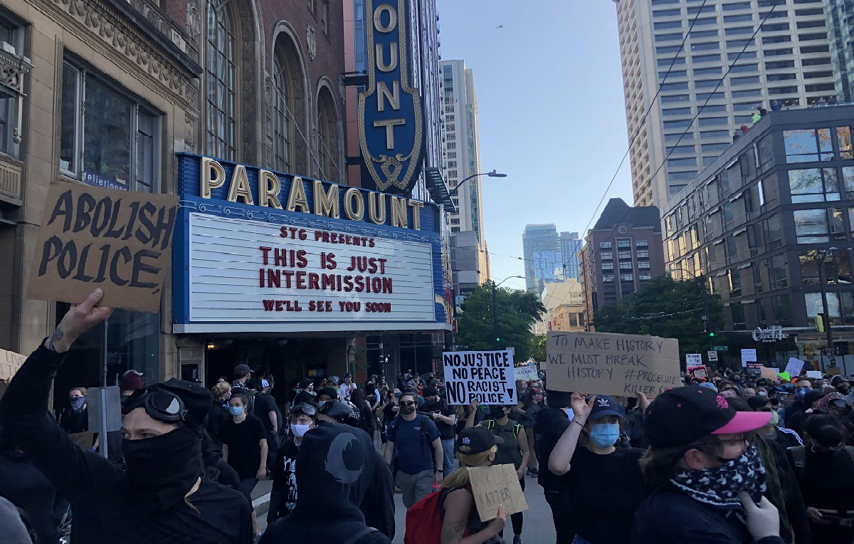 Protesters hold up signs calling for police abolition in front of the Paramount Theater.