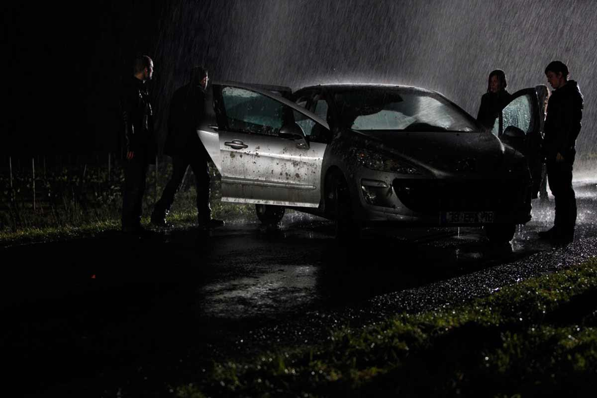 Four people surround a crashed car. All the doors are opened. It's raining.