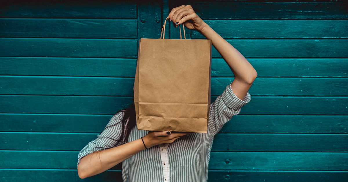 A person holding a large paper bag in front of their face