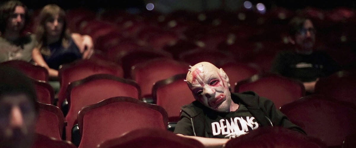 A man in a monster mask sits in a movie theatre.