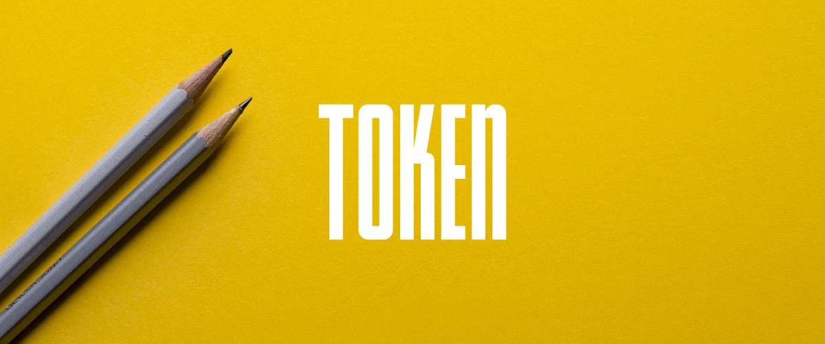 The Token logo on top of a photo of two gray pencils on a yellow background.