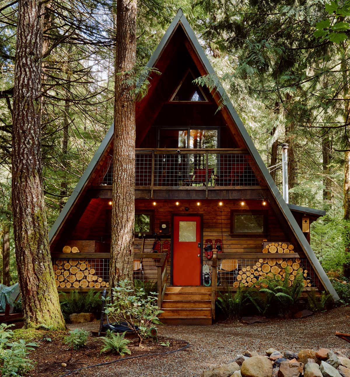 An A-frame house surrounded by pine trees in Washington state.