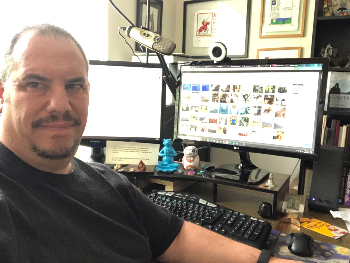 The author, MJ Blehart,in front of two monitors, at his desk working on a blog.