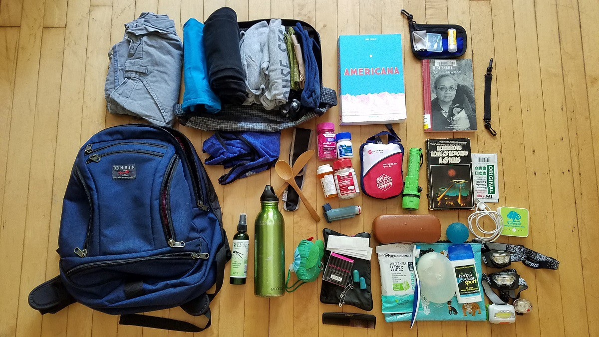Backpack pictures with a variety of camping essentials, clothing and some books