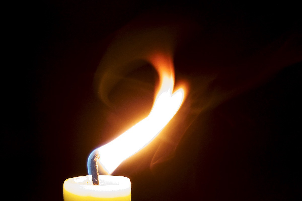 A candle with the flame bending in the wind.