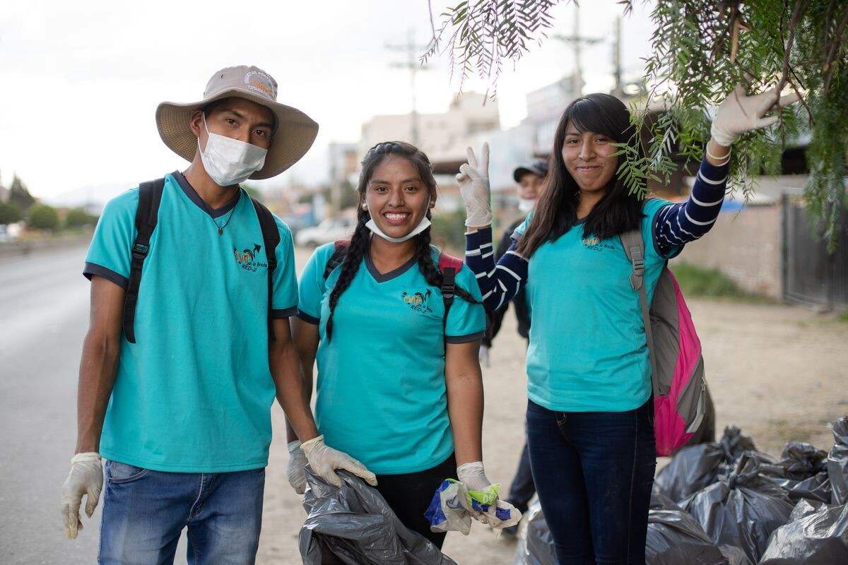 In Bolivia, three teens, two girls and a boy, are wearing blue t-shirts and are taking a break from picking up trash.