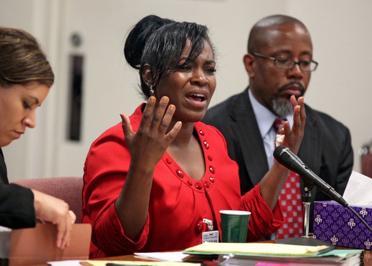 A photo of Kelley Williams-Bolar speaking into a microphone. She sits between two people.