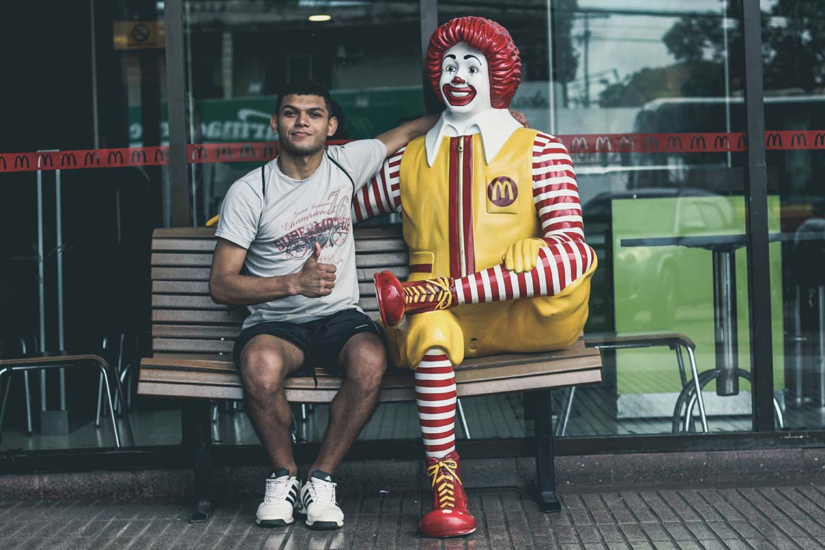 man sits on bench with Ronald McDonald statue