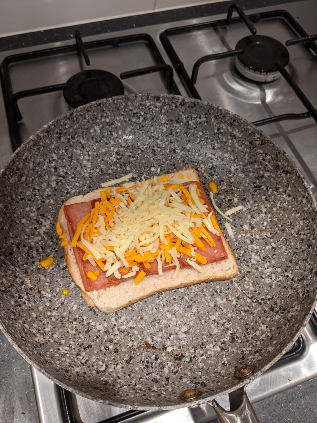 A spam and cheese toastie being cooked in a pan on a hob.