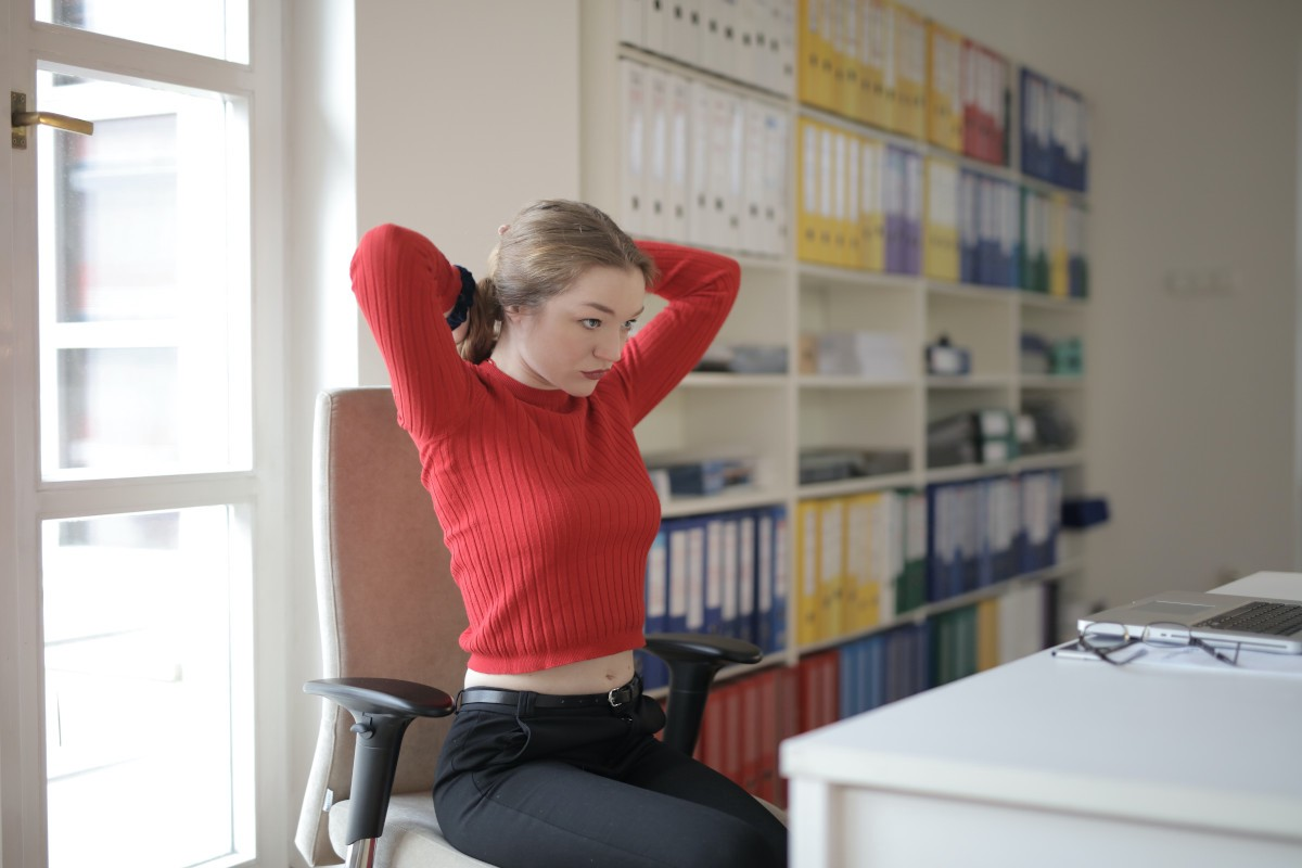 A stern woman sitting at a desk ties back her hair as through she means business.
