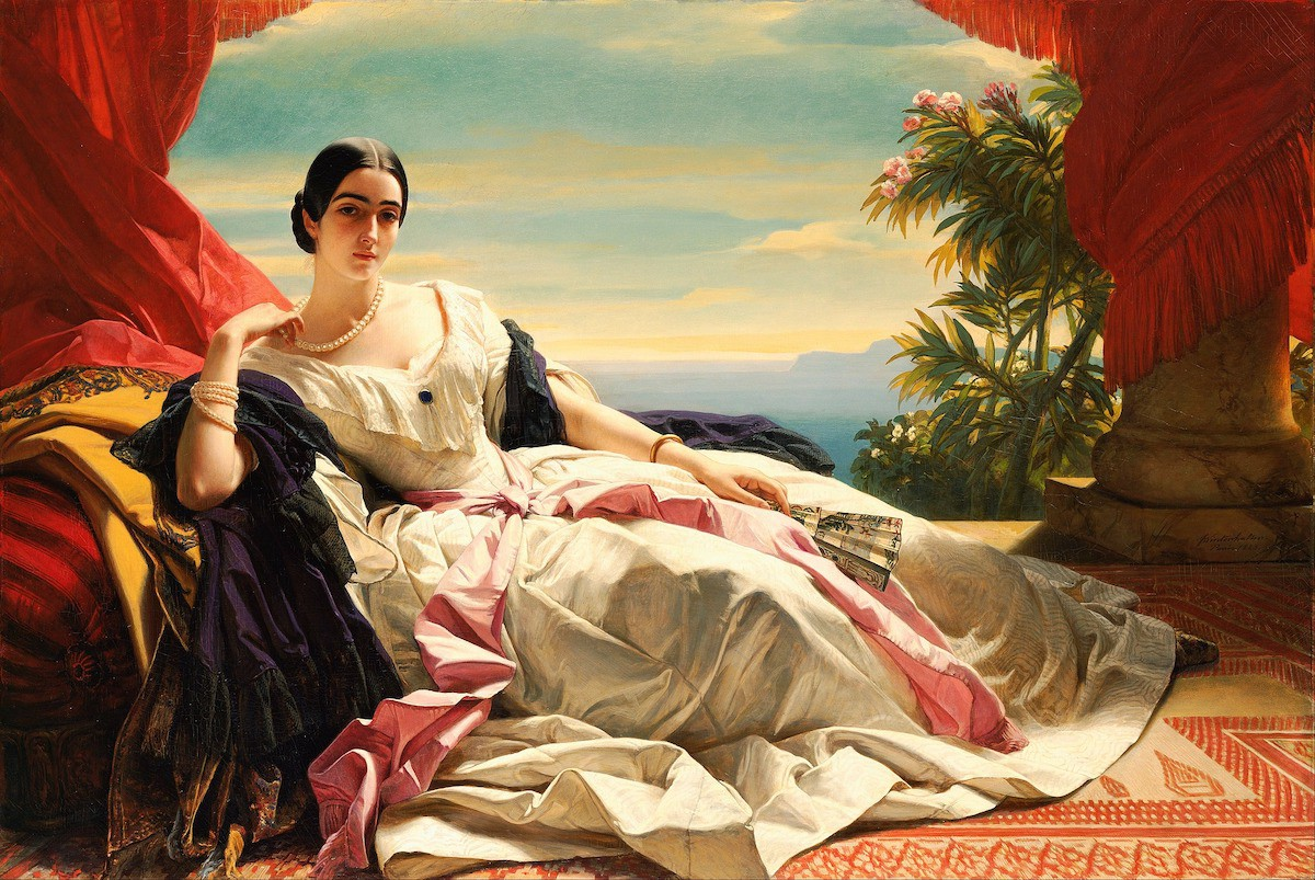 A woman in a fancy dress reclining on a couch.