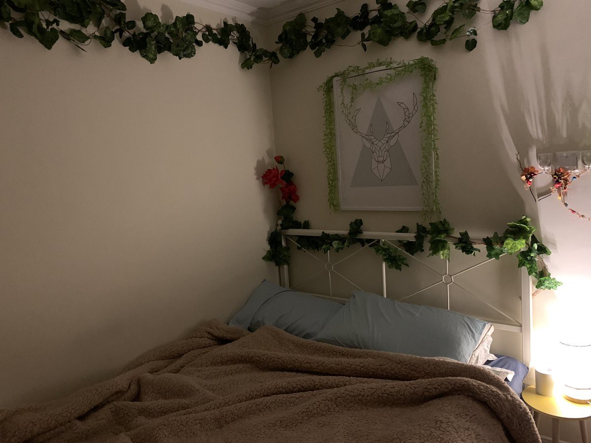 A bed with fake ivy wrapped around the bedframe, and more fake vines on the walls and over a picture frame on the wall.