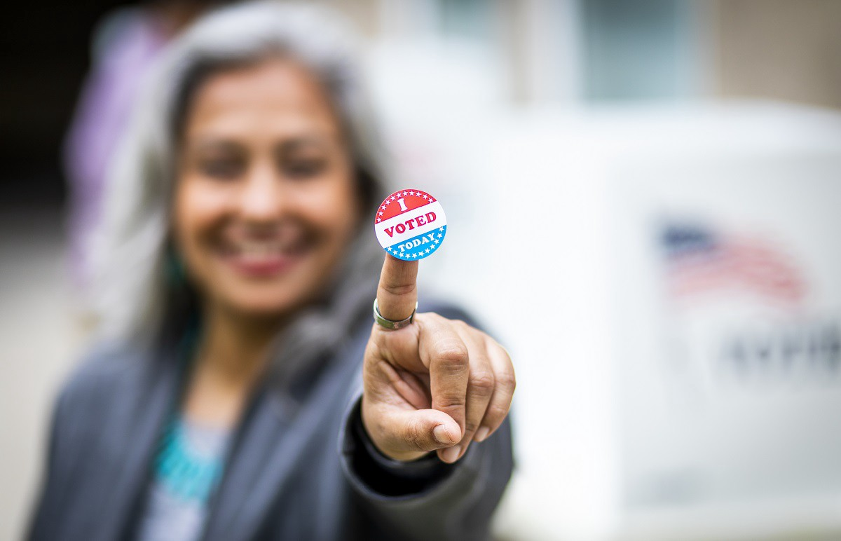 """A gray-haired woman holds up a sticker that reads, """"I voted."""""""