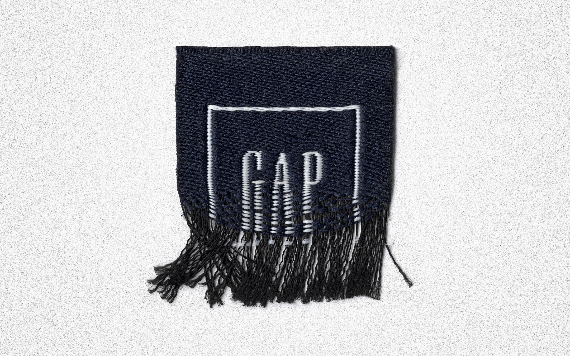 The fabric hang tag with The Gap logo unravels and falls apart.