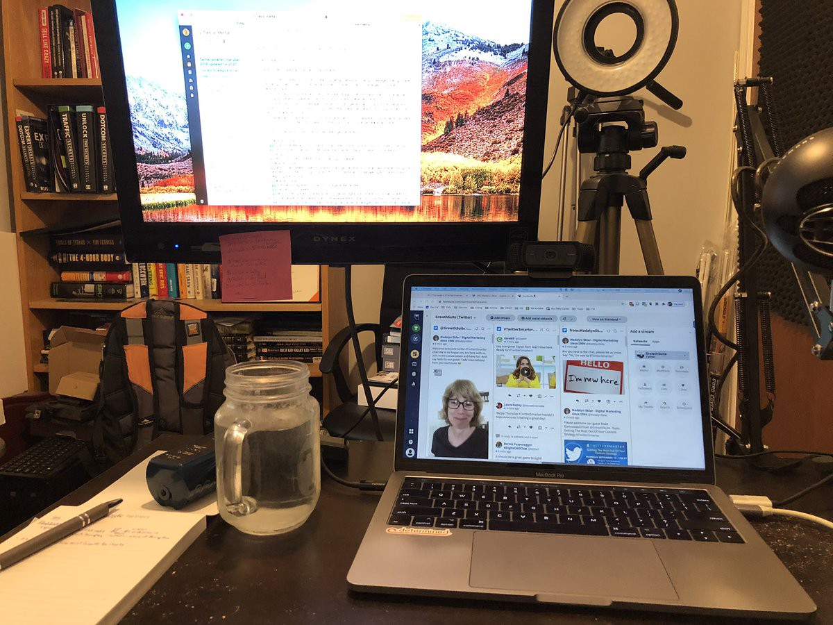 Desk in a home office with a laptop, jar of water, pen and note pad.