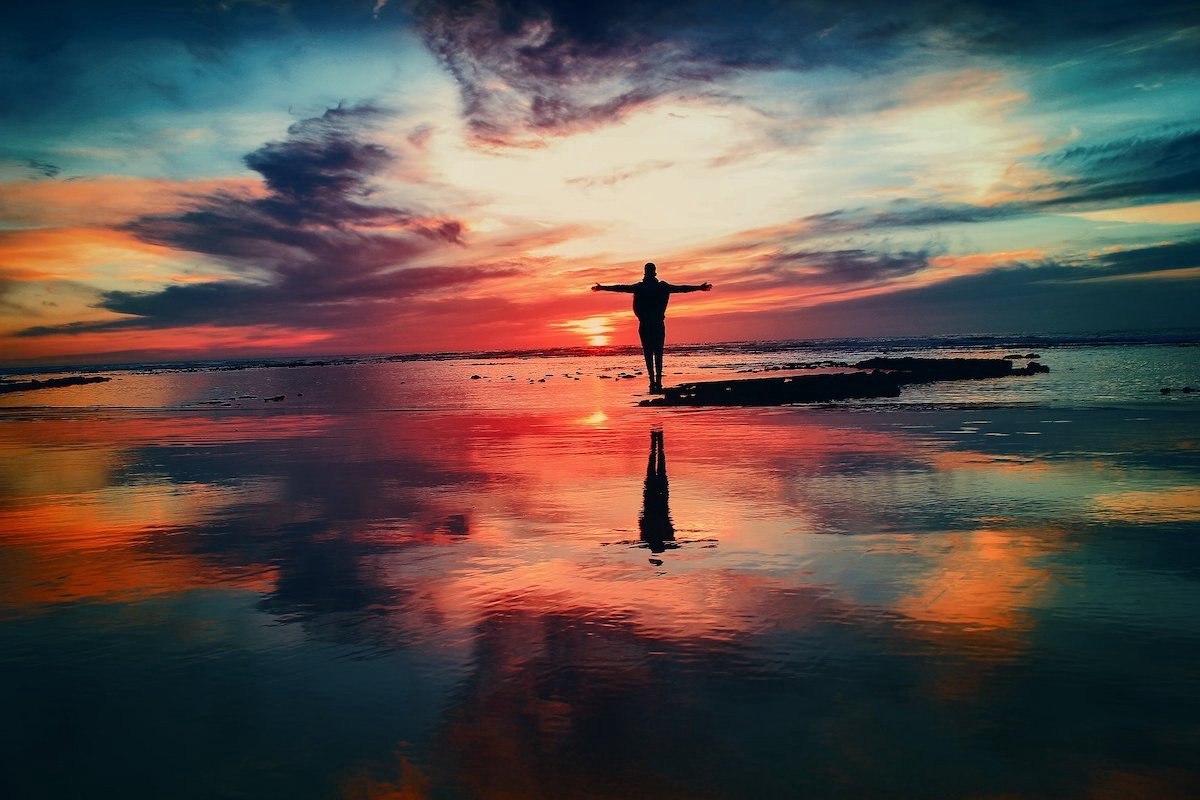 A person standing at the edge of the ocean, arms spread, amidst a colorful sunset.