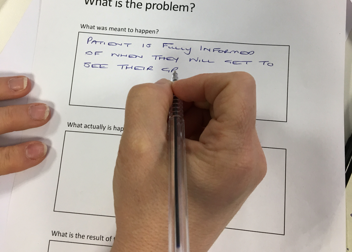 Participant writing a problem statement based on user research