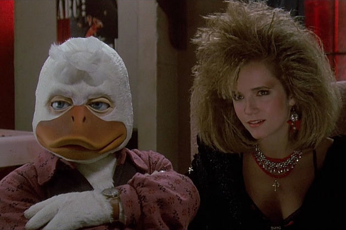 Still of Howard T. Duck (Chip Zien) and Beverly Switzer (Lea Thompson) looking sternly off-camera.
