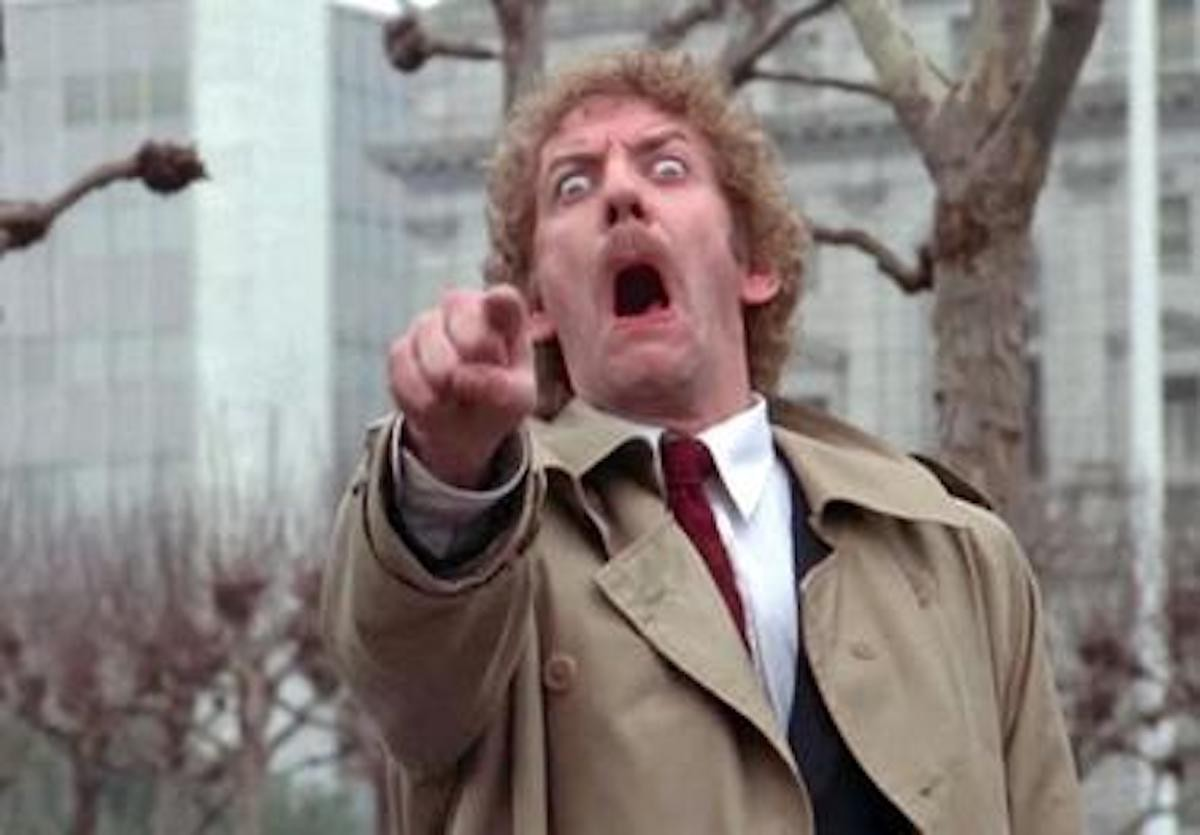 The actor Donald Sutherland in a famous scene from the 1978 film. He stares, opens his mouth, points at the camera and yells.