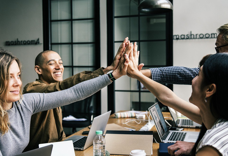 Office team at conference table all combining for a high five at the center. Laptops are in front of each as they smile.