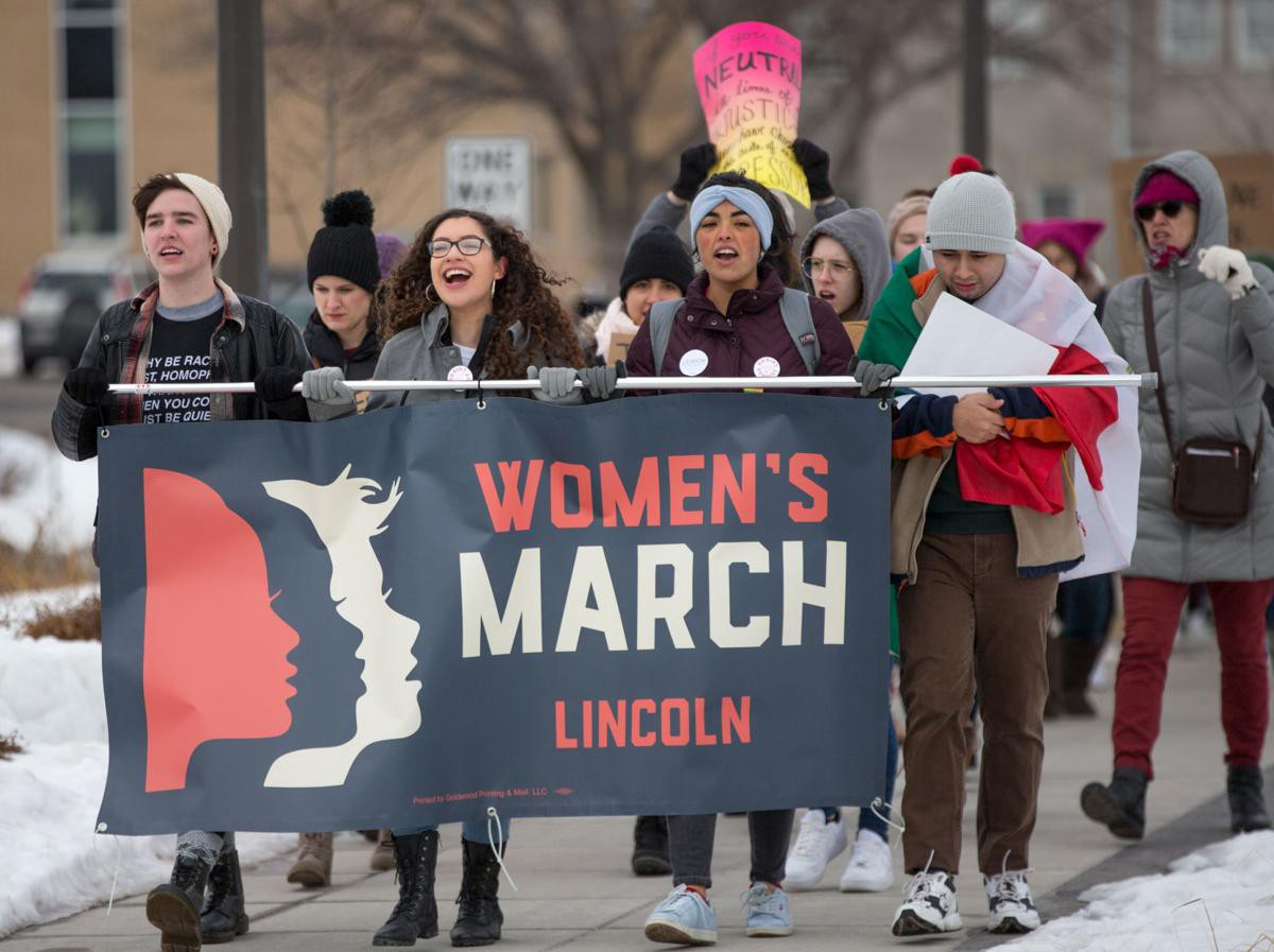 Picture of (left to right) Mar Lee, Guadalupe Esquivel, and Arlenne Rodriguez holding the 2019 Lincoln Women's March banner.