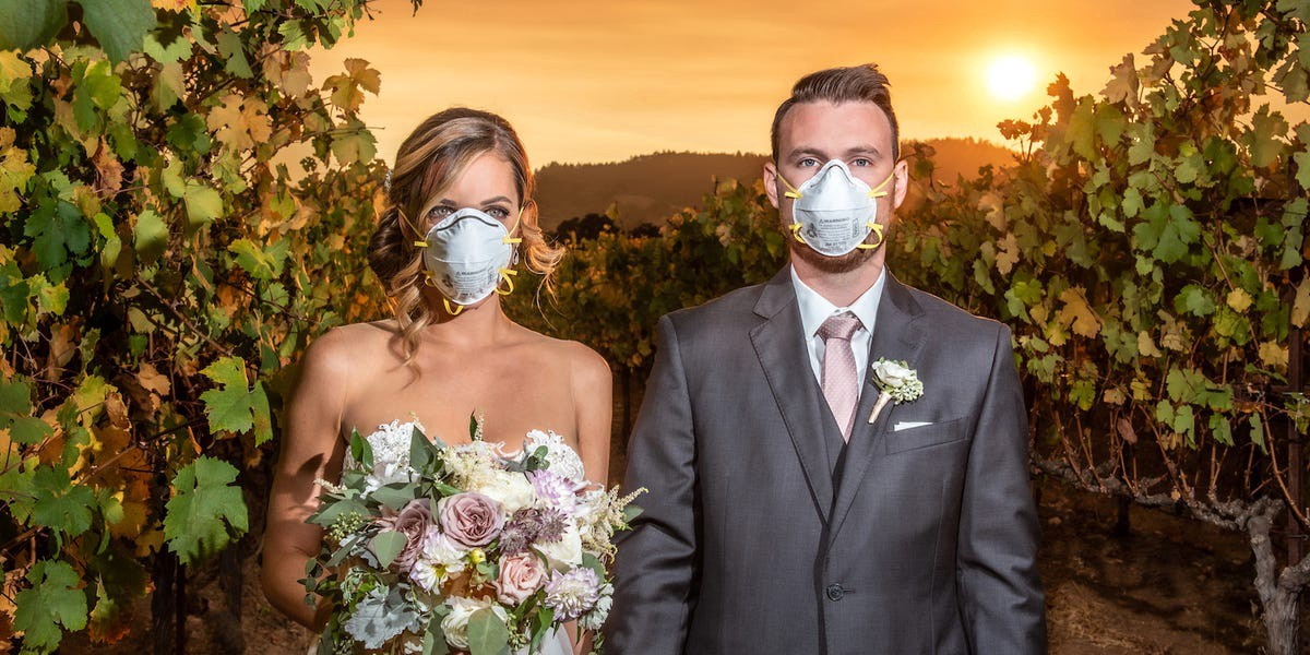 A couple in their wedding outfit and surgical masks, in a California vineyard, in front of an orange, wildfire sky.