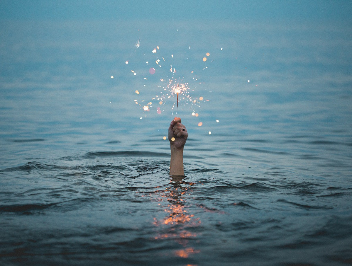 person holding sparkler above water