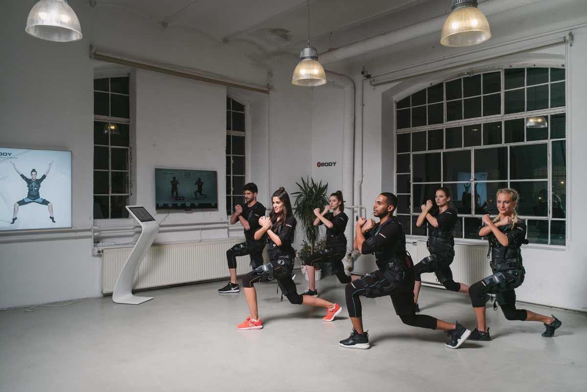 A group of people exercising with an XBody device that is in front of them.