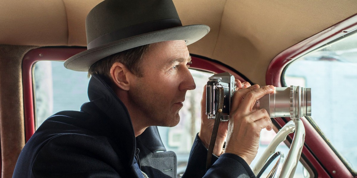 """Edward Norton's character adjusts a camera in a car seat observing his mark in """"Motherless Brooklyn."""""""