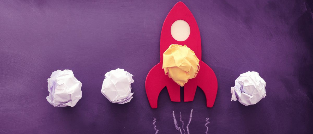 Cutout rocket ship with scrunched up post-it notes, signifying launching or boosting an idea