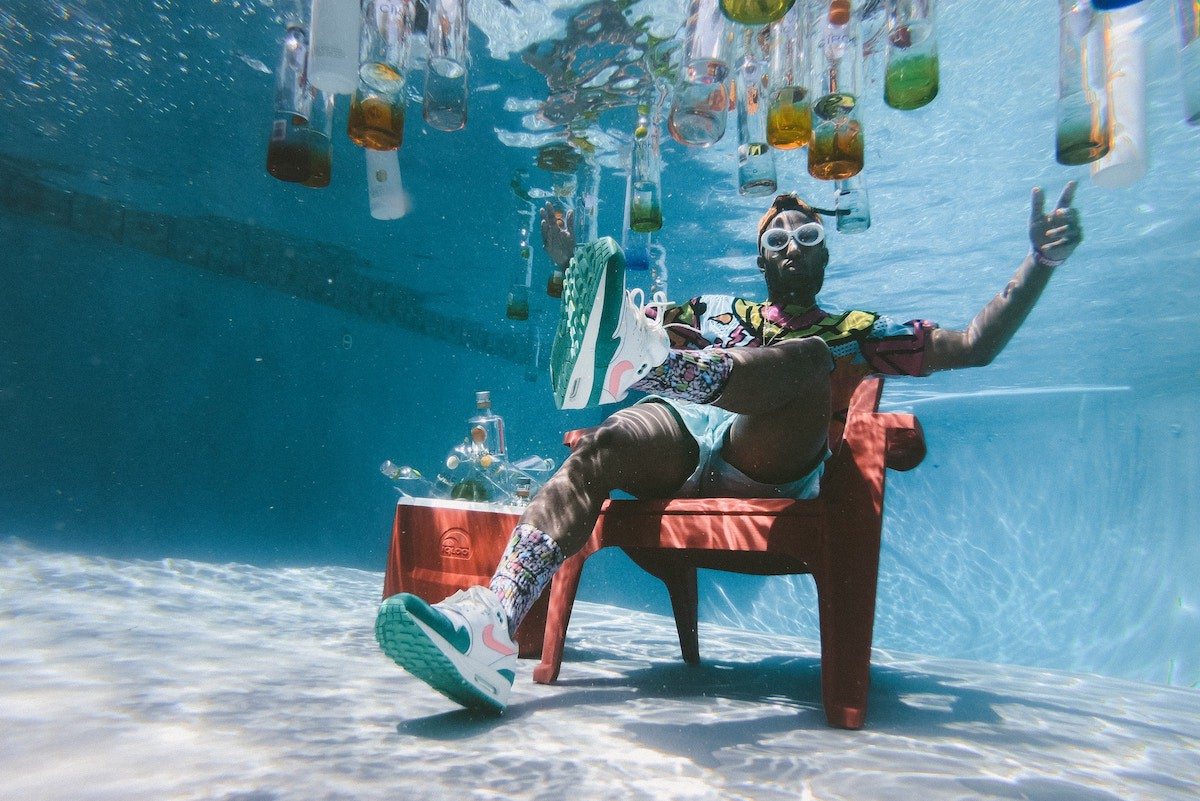 man sitting alone at the bottom of a pool with beverages floating around him