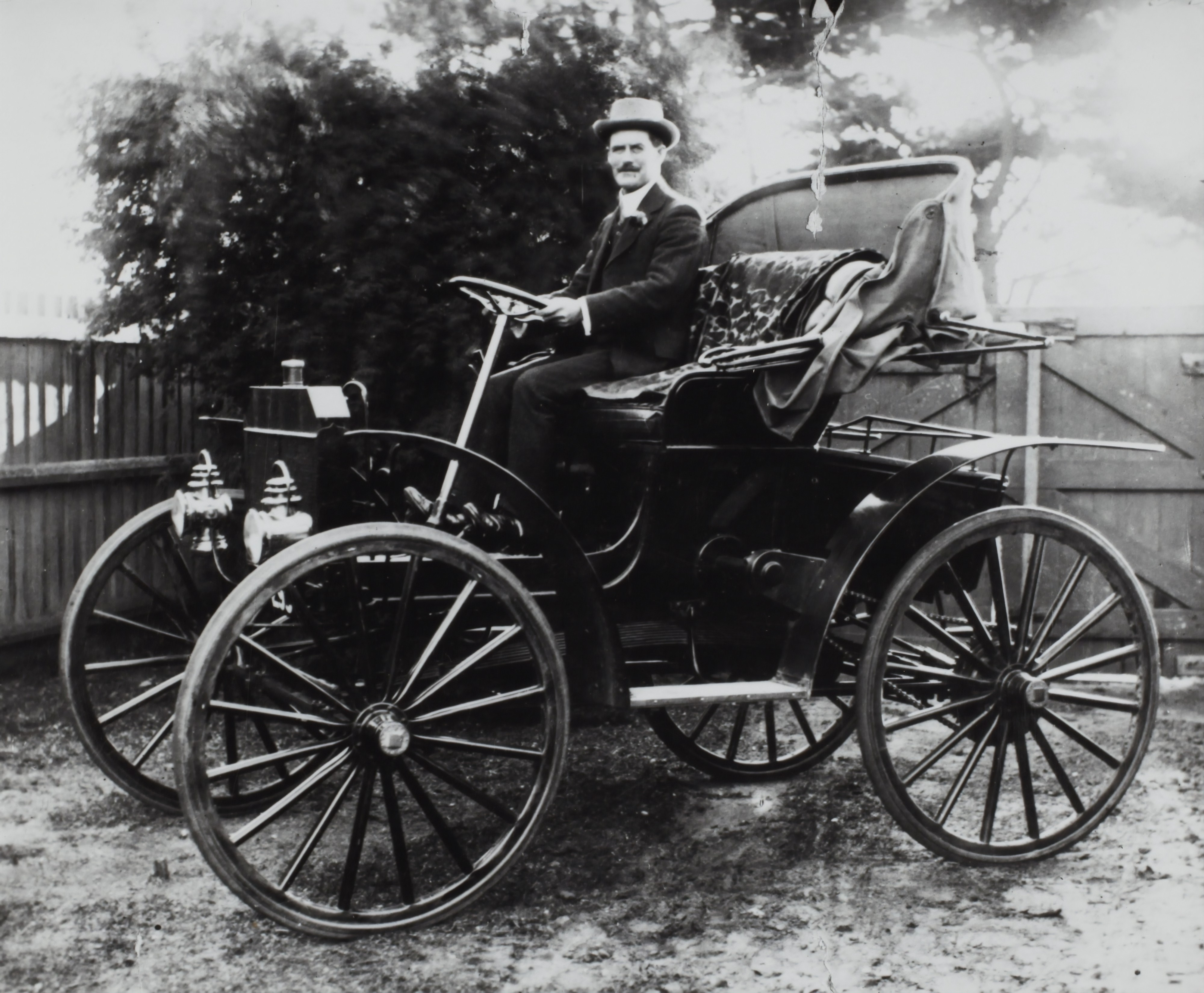 An original horseless carriage in black and white with a man in a hat sitting in the driver's seat